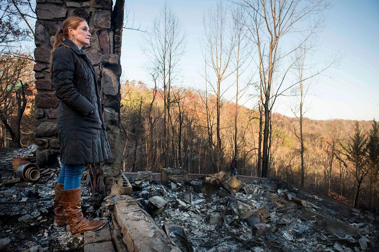 หญิงชาวเมืองแกทลินเบิร์ก มองดูสภาพความเสียหายจากไฟป่าด้วยความเศร้า
