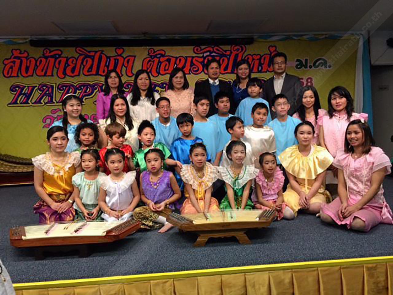 ลูกหลานไทย คณะครูอาสาจากคณะครุศาสตร์ จุฬาฯ ถ่ายภาพกับเยาวชนและผู้ปกครอง ที่ร่วมแสดงนาฏศิลป์และดนตรีไทย ในงานฉลอง ปีใหม่ของวัดไทย กรุงวอชิงตัน ดี.ซี. มีผู้มาร่วมงานอย่างครึกครื้นมากมาย.