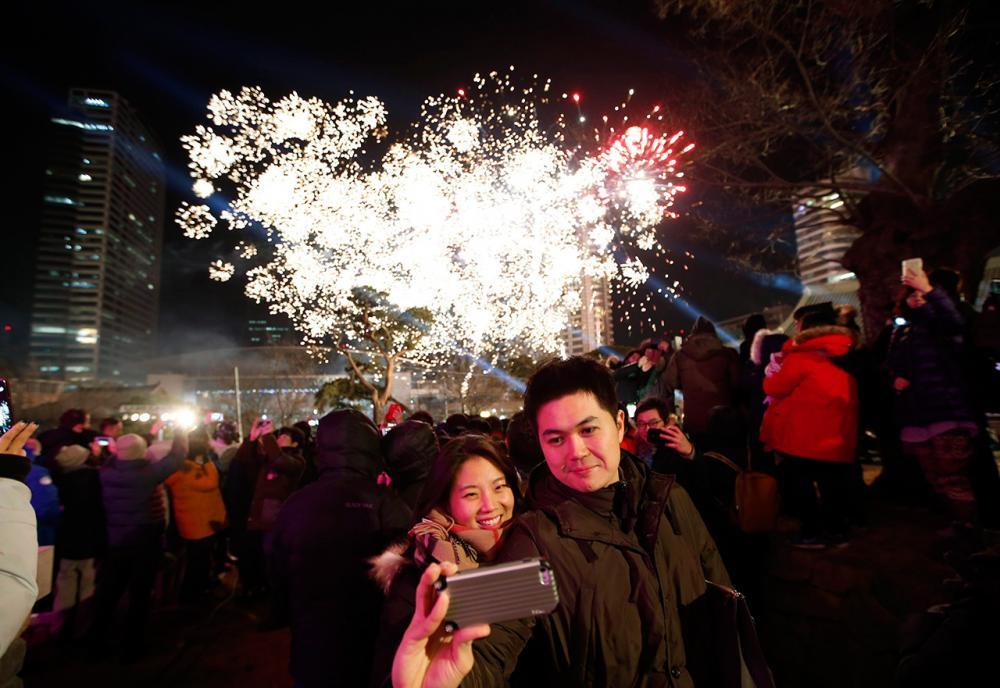 คู่รักชาวเกาหลีใต้คู่หนึ่งถ่ายรูปเซลฟี โดยมีดอกไม้ไฟที่จุดขึ้นมาพอดีเป็นฉากหลัง