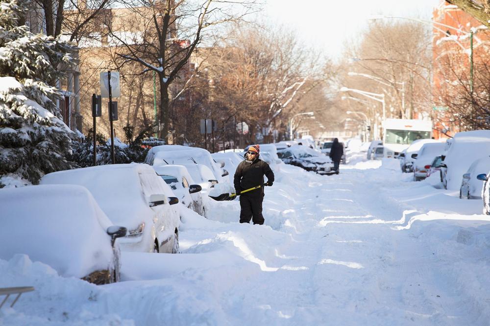 ชายคนหนึ่งพยายามจะขุดรถของตัวเองออกจากหิมะที่ตกอย่างหนักในเมืองชิคาโก (ภาพ: AFP Photo)