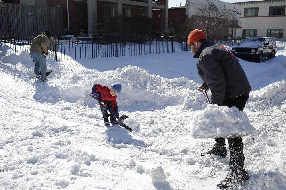 ครอบครัวชาวเมืองดีทรอยต์ช่วยกันตักหิมะที่กีดขวางถนน (ภาพ: AFP Photo)