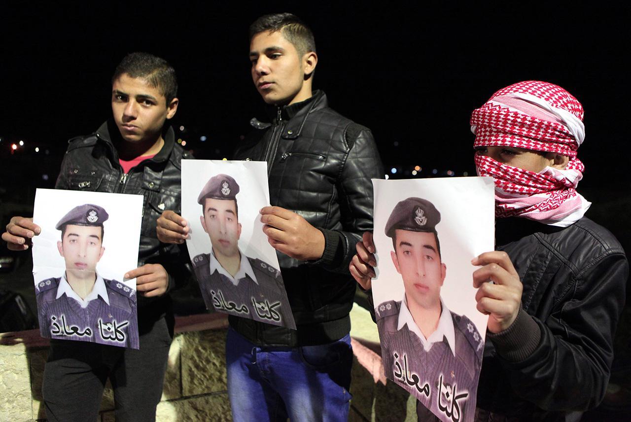 บรรดาญาติถือภาพของนาย มูอัซ อัล-คาซาสเบห์ (ภาพ: REUTERS)