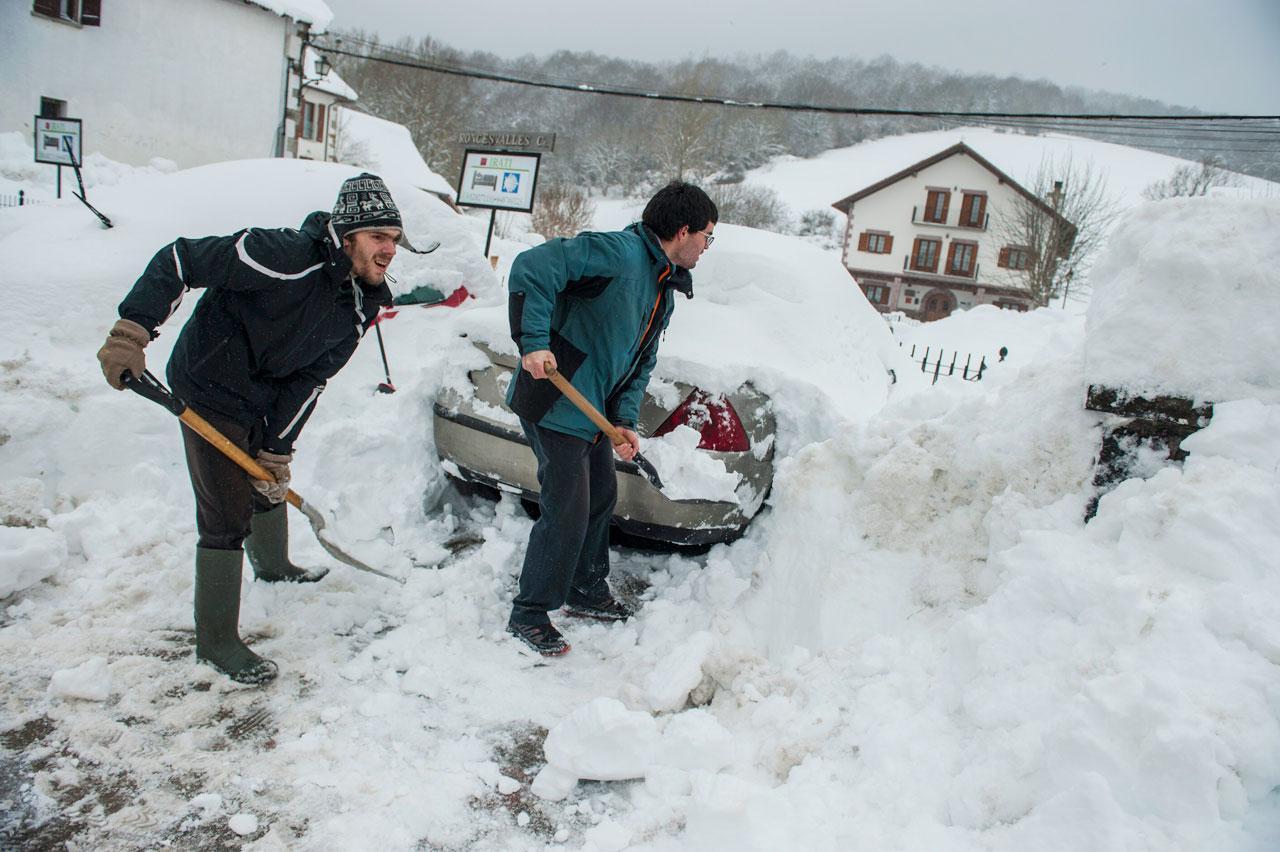 สองหนุ่มช่วยกันตักหิมะที่ปกคลุมรถยนต์จนมิดหมดทั้งคันใน เมืองเอล เอสปินอล