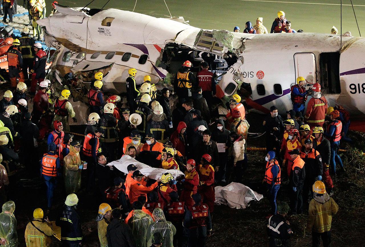 เจ้าหน้าที่ลำเลียงศพผู้เสียชีวิตออกมาจากซากเครื่องบิน (ภาพ: REUTERS)