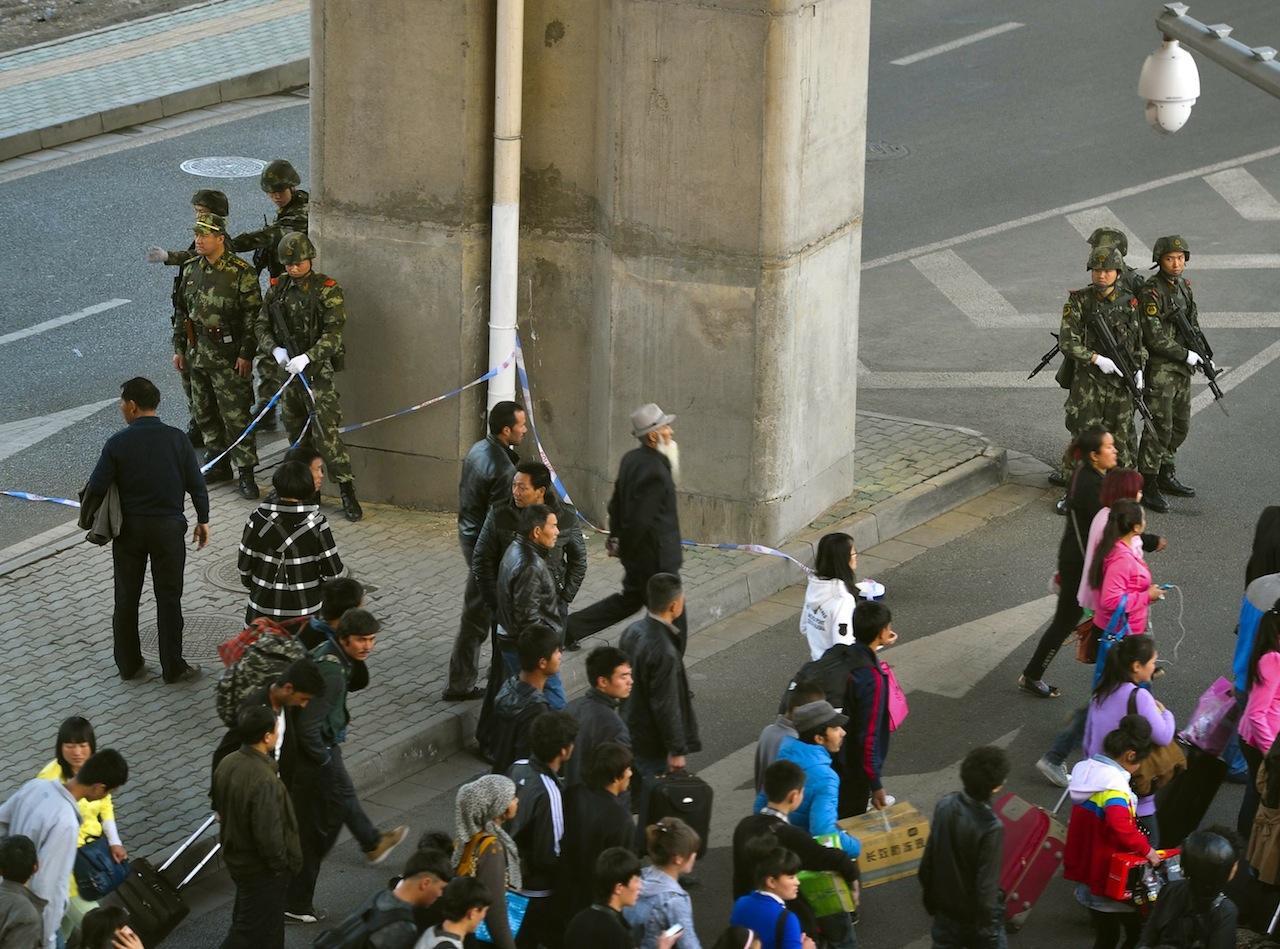 กลุ่มจีนมุงยืนมองสถานการณ์ที่สถานีรถไฟในเมืองอูหลู่มู่ฉี ขณะที่หน่วยสารวัตรทหารยืนรักษาความปลอดภัย