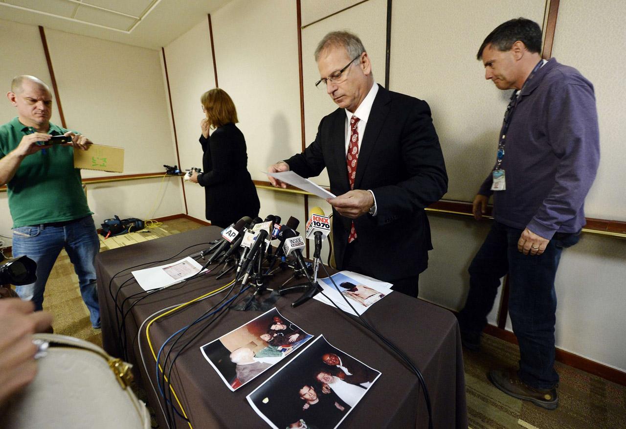 โชว์หลักฐานรูปถ่ายให้นักข่าวดู ระหว่างเปิดแถลงข่าวที่เบเวอร์รีย์ ฮิลล์ ในนครลอสแองเจลิส เมื่อ 5พ.ค.