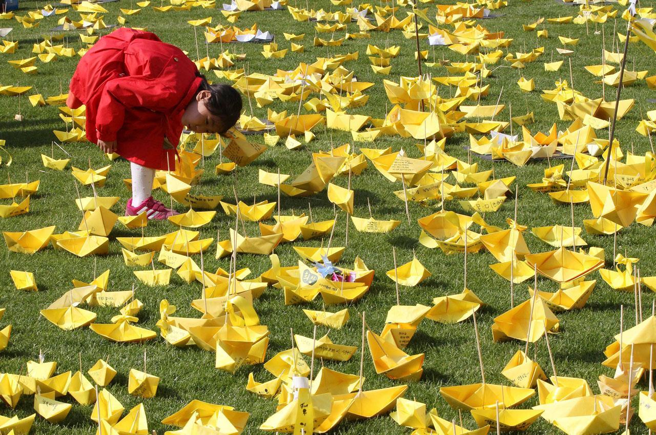 เด็กหญิงเกาหลีใต้พับเรือกระดาษสีเหลืองมาร่วมวางไว้อาลัยผู้เสียชีวิต