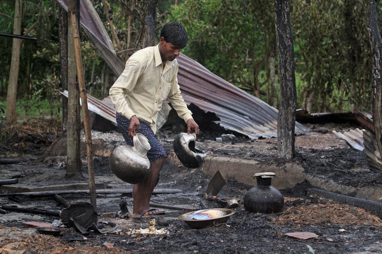 ชาวบ้านเก็บข้างของที่ยังพอใช้ได้ออกจากซากบ้านที่ถูกไฟไหม้