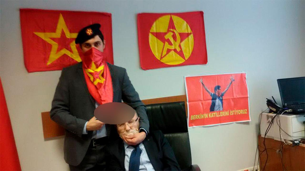 ชายสวมสูทโพกผ้าที่มีลวดลายเหมือนธงของกลุ่ม DHKP-C จับอัยการคีราซเป็นตัวประกัน (ภาพ: REUTERS)