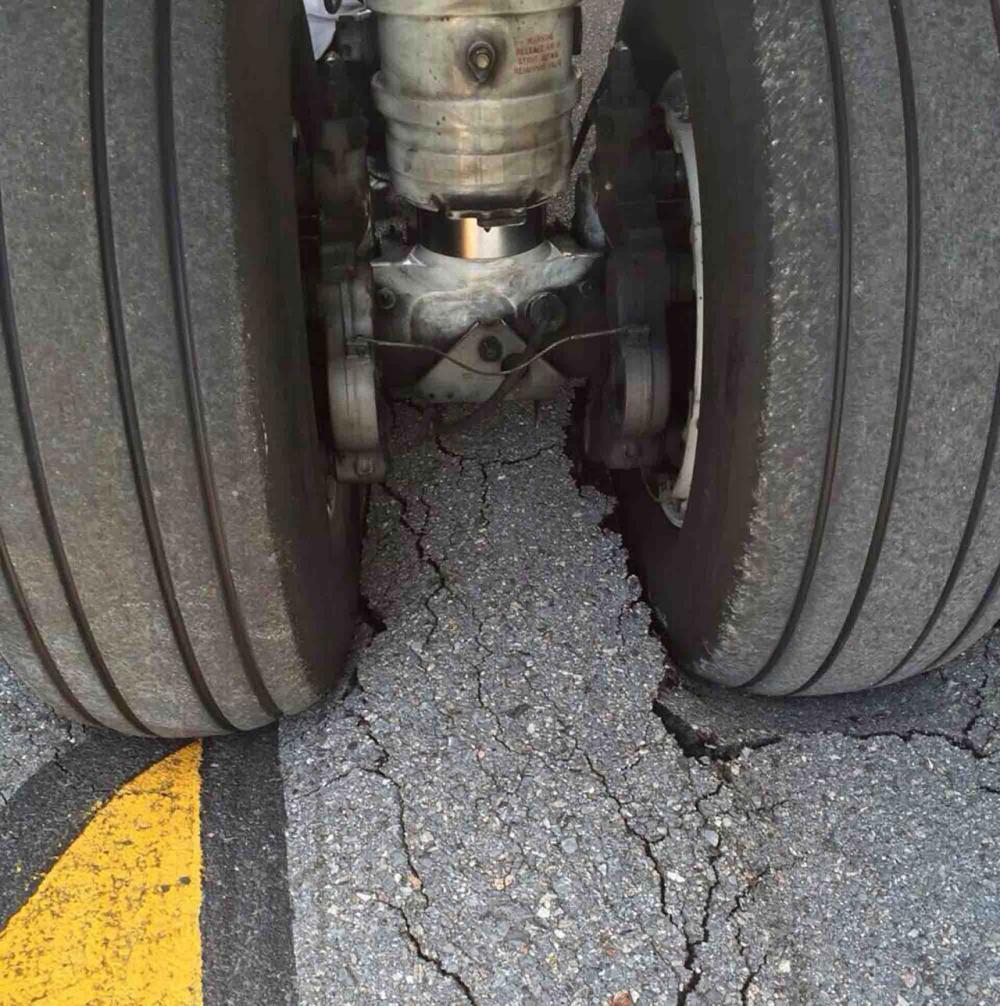 ล้อเครื่องบินที่จมไปในพื้นยางมะตอยที่แตก