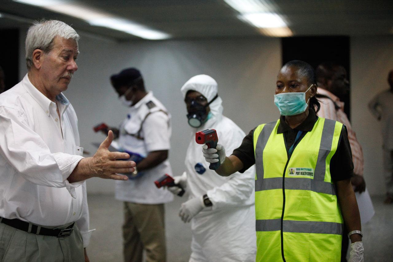 เจ้าหน้าที่ไนจีเรียตรวจวัดอุณหภูมิร่างกายของผู้โดยสารขาเข้า ที่ท่าอากาศยานในกรุงลากอส สกัดอีโบลาระบาด