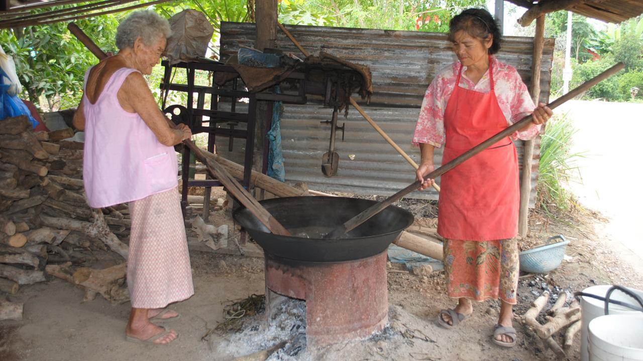คุณยายประทุม ถนอมวงค์ อายุ 88 ปี และนางทวีป ถนอมวงค์ อายุ 60 ปี สองแม่ลูก กวนขนมกระยาสารทในกระทะใบบัว