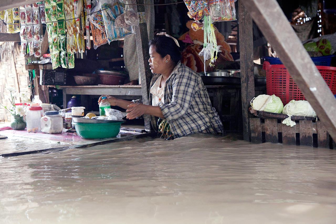 แม่ค้าต้องค้าขายทั้งๆที่น้ำท่วม (ภาพ: AP)