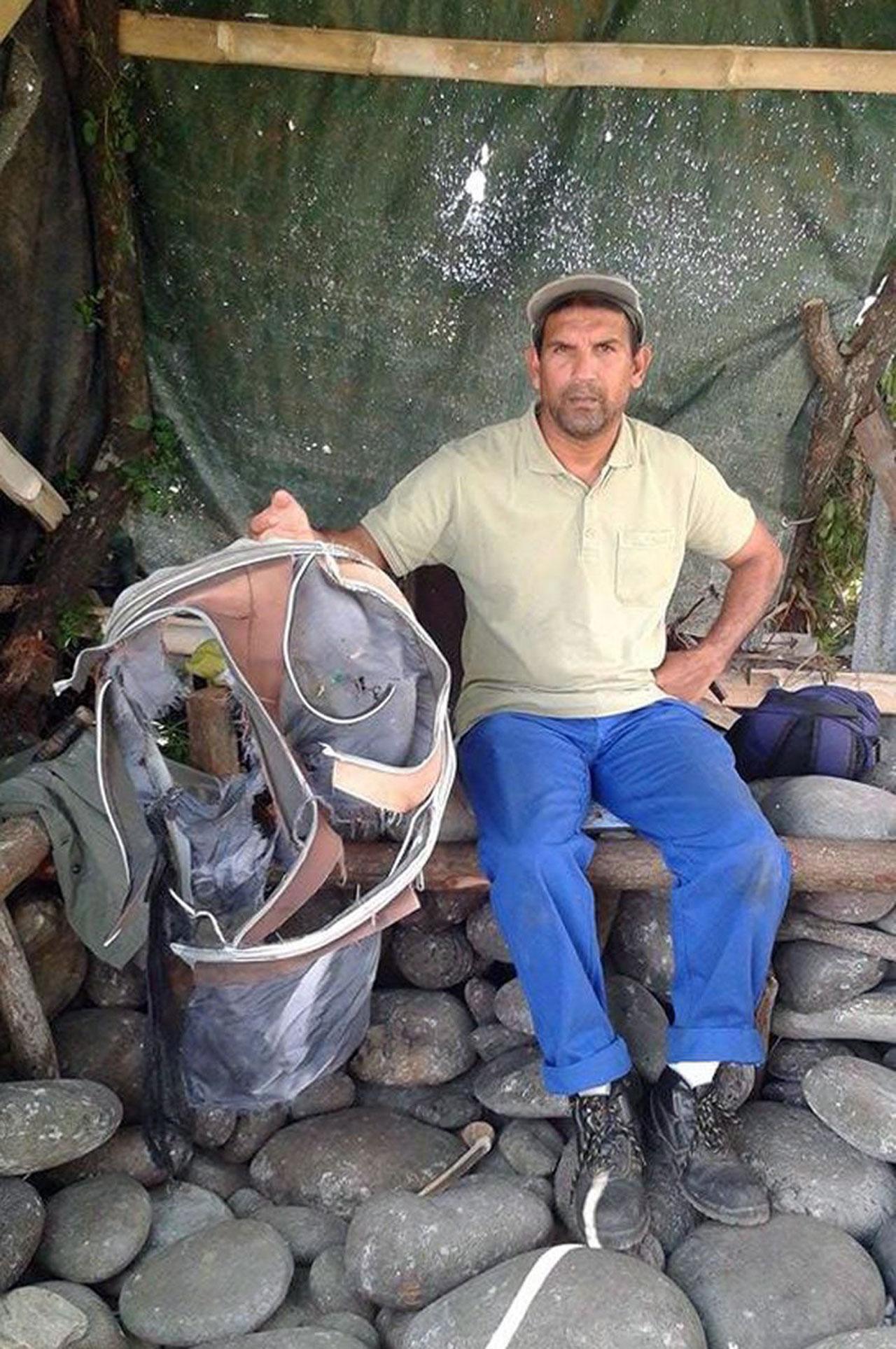 ดังไม่เจตนา–นายจอห์นนี เบเก้ คนสวนของสภาเมืองแซงต์อองเดร บนเกาะเรอูนียงของฝรั่งเศส หนึ่งในพนักงานทำความสะอาดชายหาด โชว์กระเป๋าต้องสงสัยที่เขาพบพร้อมชิ้นส่วนปีกเครื่องบินโบอิ้ง 777 เป็นคนแรก ซึ่งอาจเป็นซากเครื่องบินเอ็มเอช 370 ที่หายสาบสูญ ไปเมื่อ 16 เดือนก่อน (เอเอฟพี)