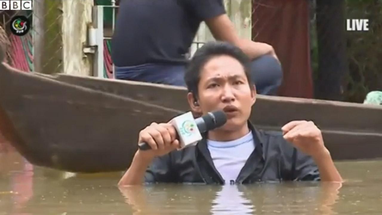 นักข่าวชายชาวเมียนมา ยืนรายงานข่าวสถานการณ์น้ำท่วม