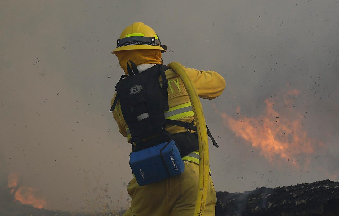 เจ้าหน้าที่ดับเพลิงฉีดน้ำดับเปลวไฟ