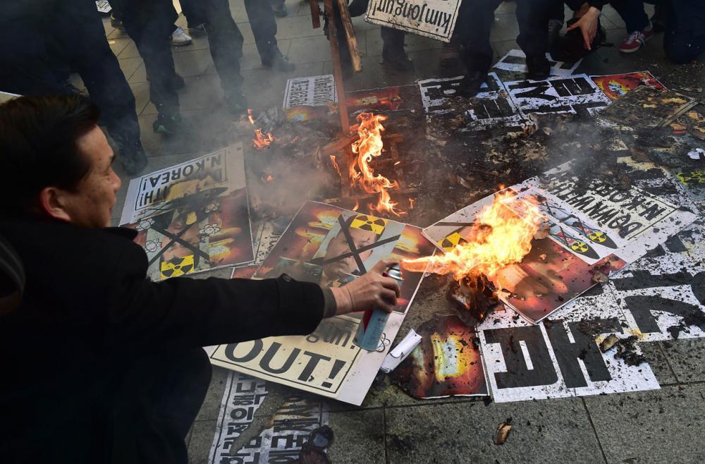 ชาวเกาหลีใต้ ในกรุงโซล จุดไฟเผารูปคิม จอง อึน ประท้วงเกาหลีเหนือทดสอบระเบิดไฮโดรเจน