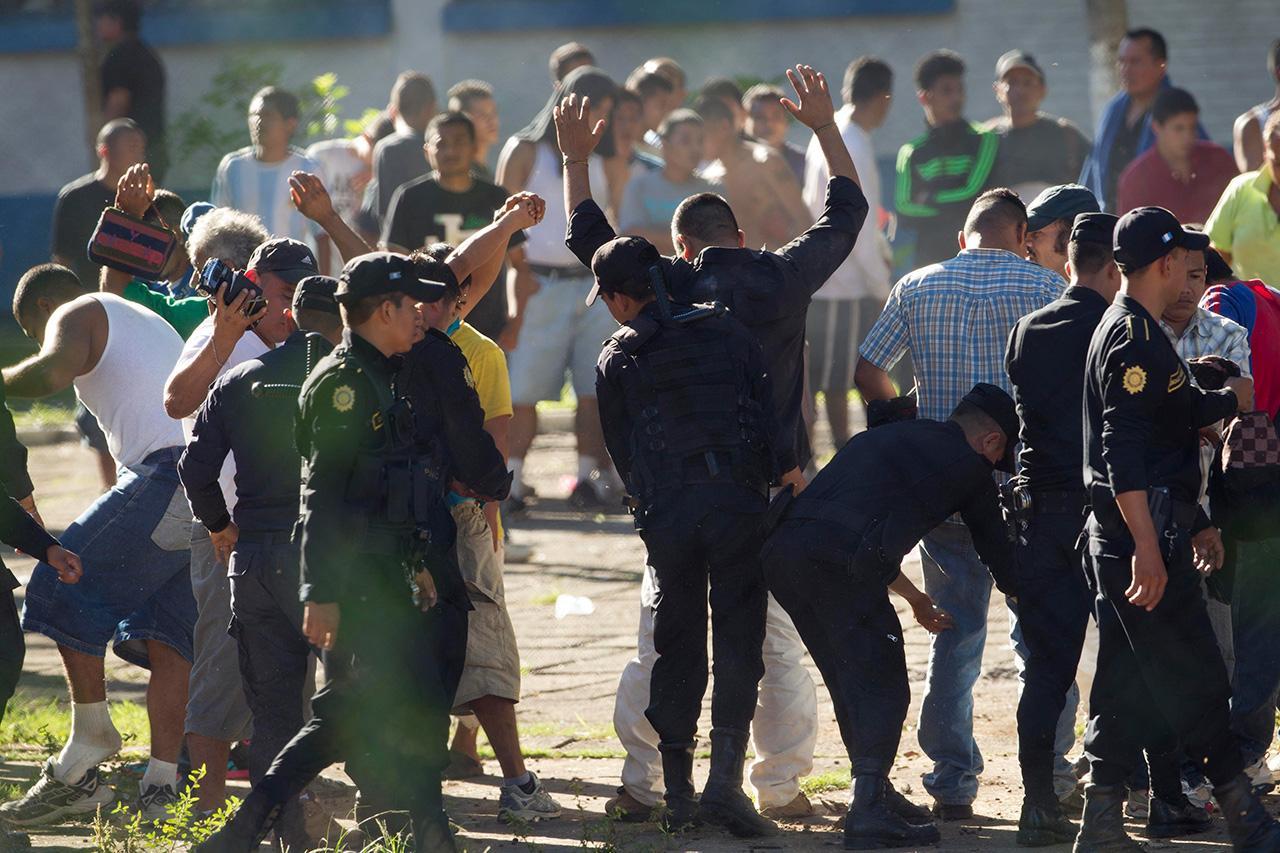 ผู้คุมเรือนจำค้นตัวนักโทษ (ภาพ: AP)