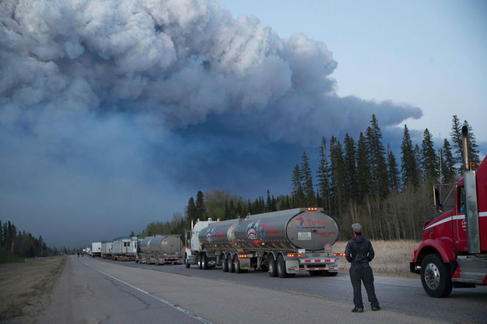 คนขับรถบรรทุกน้ำมันยืนดูกลุ่มควันไฟหนาทึบจากไฟไหม้ป่าในเมืองฟอร์ต แม็คเมอร์เรย์