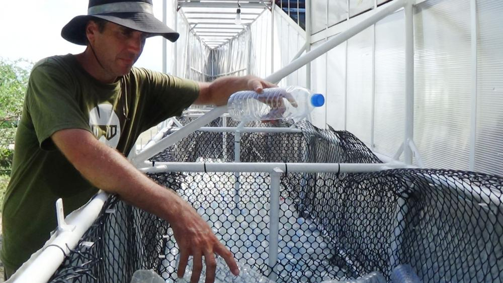 เคิร์ก กิลล็อก กำลังเก็บขวดพลาสติกใส่ในตัวเรือ