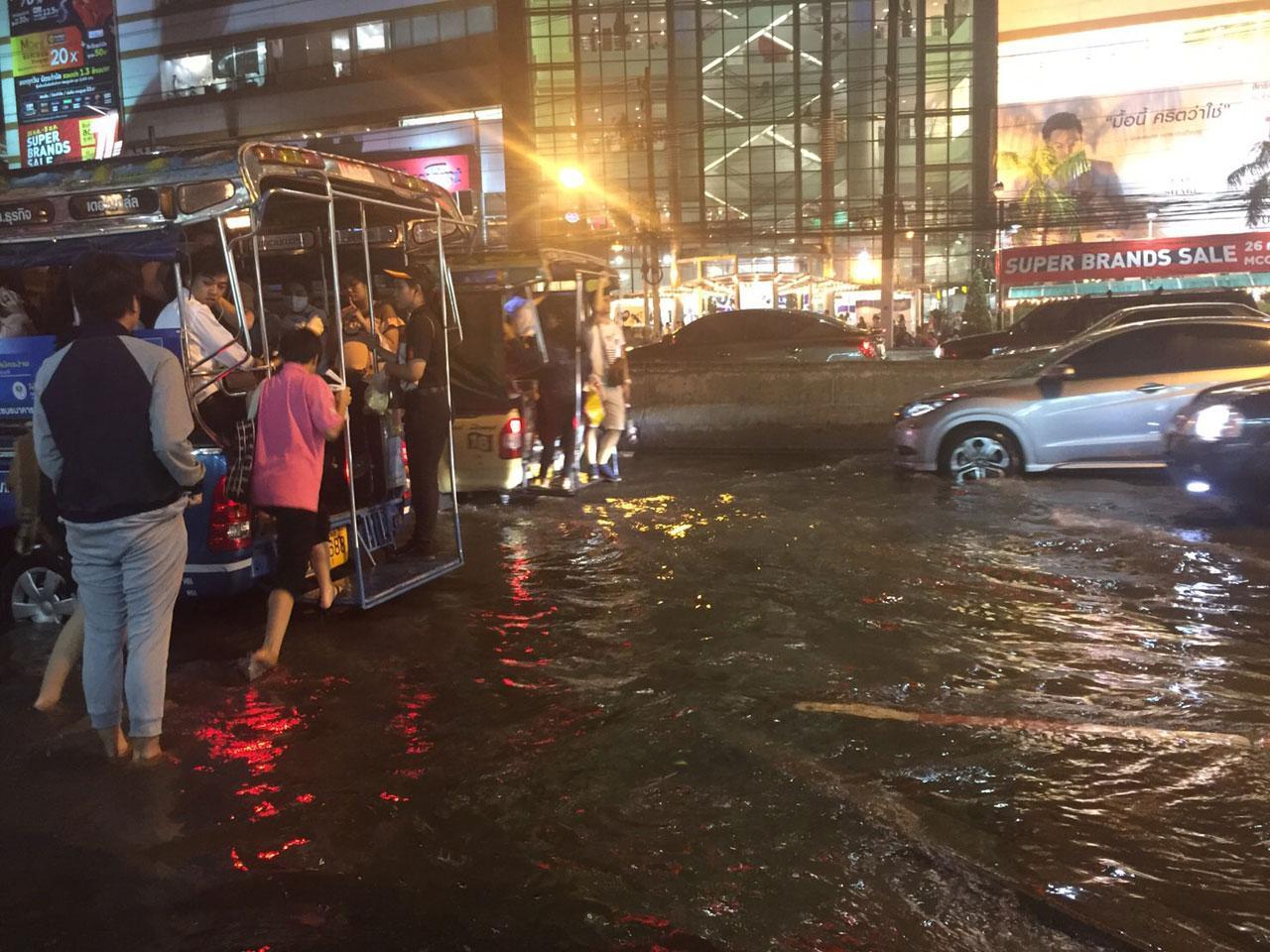 ประชาชนเดินทางด้วยรถโดยสาร ถอดรองเท้าเดินลุยน้ำ