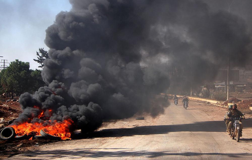 นักรบกบฏ กองพันจาอิช อัล ฟาตาห์จุดไฟเผายางรถ บริเวณทางเข้าเมืองอเลปโป ทางตะวันตกเฉียงใต้ของเขตแนวหน้า เมื่อ3พ.ย.