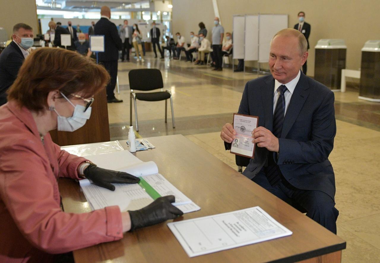 ประธานาธิบดีวลาดิเมียร์ ปูติน แห่งรัสเซีย โชว์หนังสือเดินทางต่อคณะกรรมการการเลือกตั้งท้องถิ่น ในกรุงมอสโก เมื่อ 1 ก.ค. 63 ซึ่งเป็นวันสุดท้ายของการลงประชามติแก้ไขรัฐธรรมนูญ
