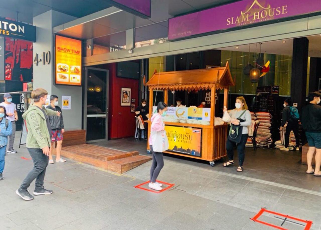 นักเรียนไทยที่ได้รับผลกระทบจากวิกฤติไวรัสโควิด-19 เข้าคิวเว้นระยะห่างทางสังคม เพื่อรับแจกข้าวสารจากน้ำใจชุมชนไทยที่ร้านสยามเฮ้าส์ ซิดนีย์.