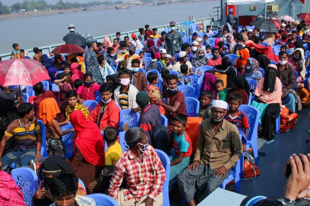 ผู้ลี้ภัยชาวโรฮีนจานั่งอยู่บนเรือของกองทัพเรือมุ่งหน้าไปยังเกาะห่างไกล พาซาน ชาร์ ในอ่าวเบงกอล