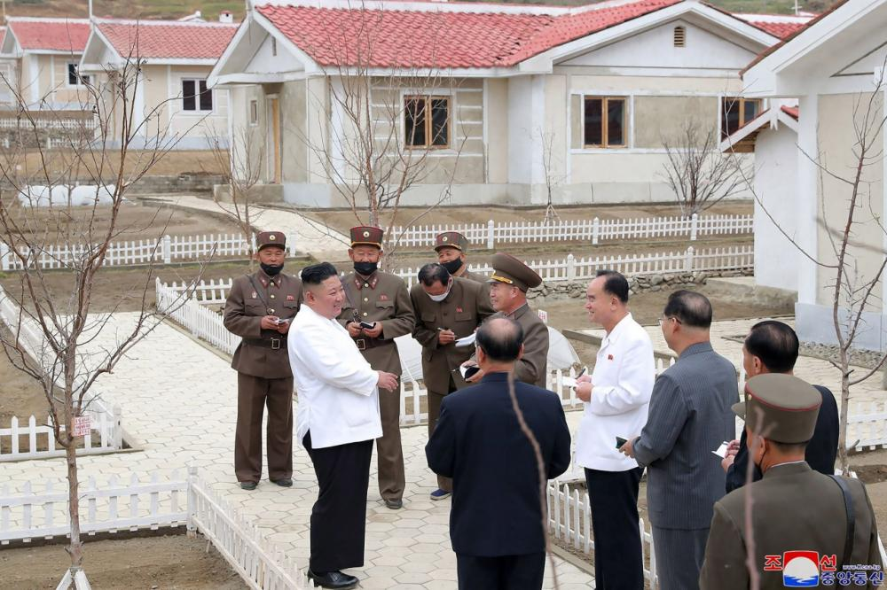 คิม จอง อึน พูดคุยกับเจ้าหน้าที่ขณะมาดูบ้านที่สร้างให้แก่ชาวบ้านประสบภัยน้ำท่วมจนบ้านพังเสียหายในเขต คิมฮวา