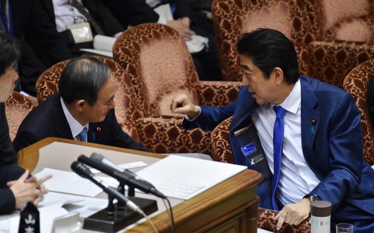 นายกรัฐมนตรีชินโสะ อาเบะ พูดคุยกับนายโยชิฮิเดะ ซูกะ ระหว่างการประชุมสภา เมื่อปี 2560