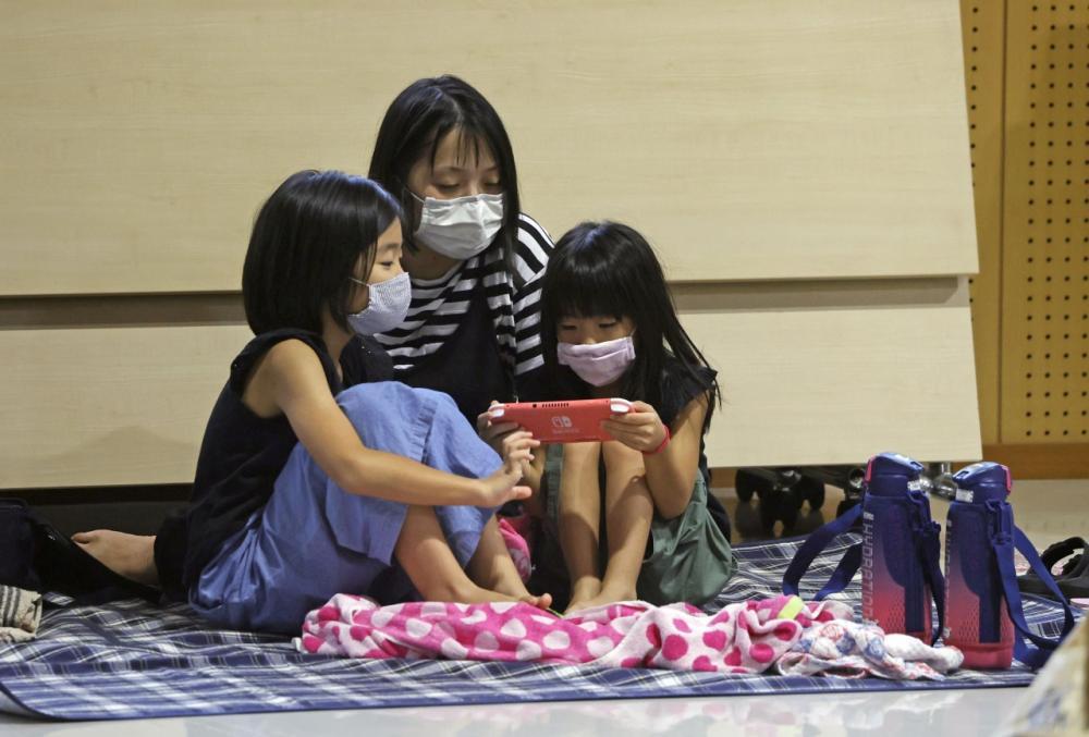 หญิงชาวญี่ปุ่นและลูกสาวสองคน อพยพมาอยู่ในศูนย์พักพิงชั่วคราว เพื่อความปลอดภัย ขณะซุปเปอร์ไต้ฝุ่น ไห่เฉิน ถล่มภาคใต้ของประเทศ