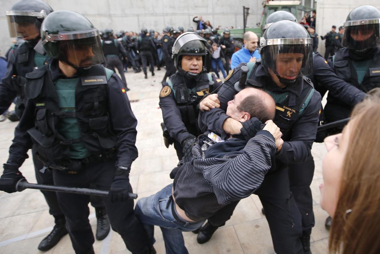 ตำรวจปราบจลาจลกำลังควบคุมตัวชายคนหนึ่ง หลังปะทะกับผู้ชุมนุม