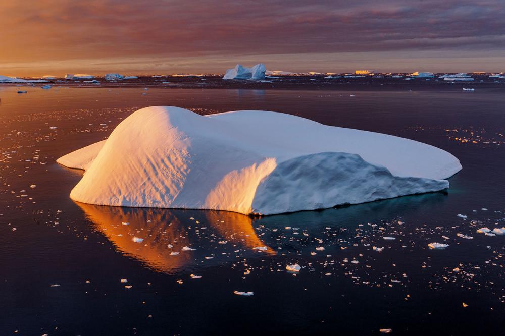 เส้นโค้งที่สวยงามของภูเขาน้ำแข็งคือประจักษ์พยานของการละลายอย่างรวดเร็วที่มันเคยเผชิญ เมื่อถูกตัดขาดจาก ธารน้ำแข็งและไหลลงสู่ช่องแคบเลอแมร์ ฤดูหนาวทางฝั่งตะวันตกของคาบสมุทรแอนตาร์กติกาอุ่นขึ้นราวห้าองศาเซลเซียสนับตั้งแต่ปี 1950