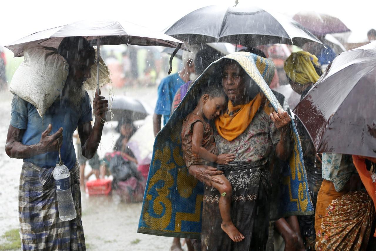 ชาวโรฮีนจาอุ้มลูกน้อย ท่ามกลางสายฝน ขณะต้องหนีภัยการสู้รบจากรัฐยะไข่