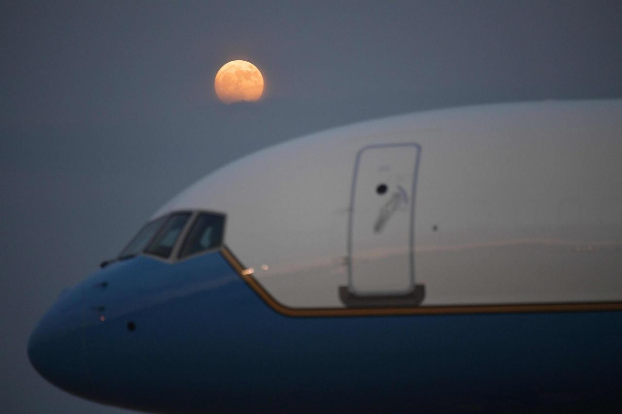 พระจันทร์เต็มดวงถูกเมฆบดบังเล็กน้อย ขณะลอยเหนือเครื่องบิน แอร์ ฟอร์ซ วัน ที่ฐานทัพอากาศ แอนดรู