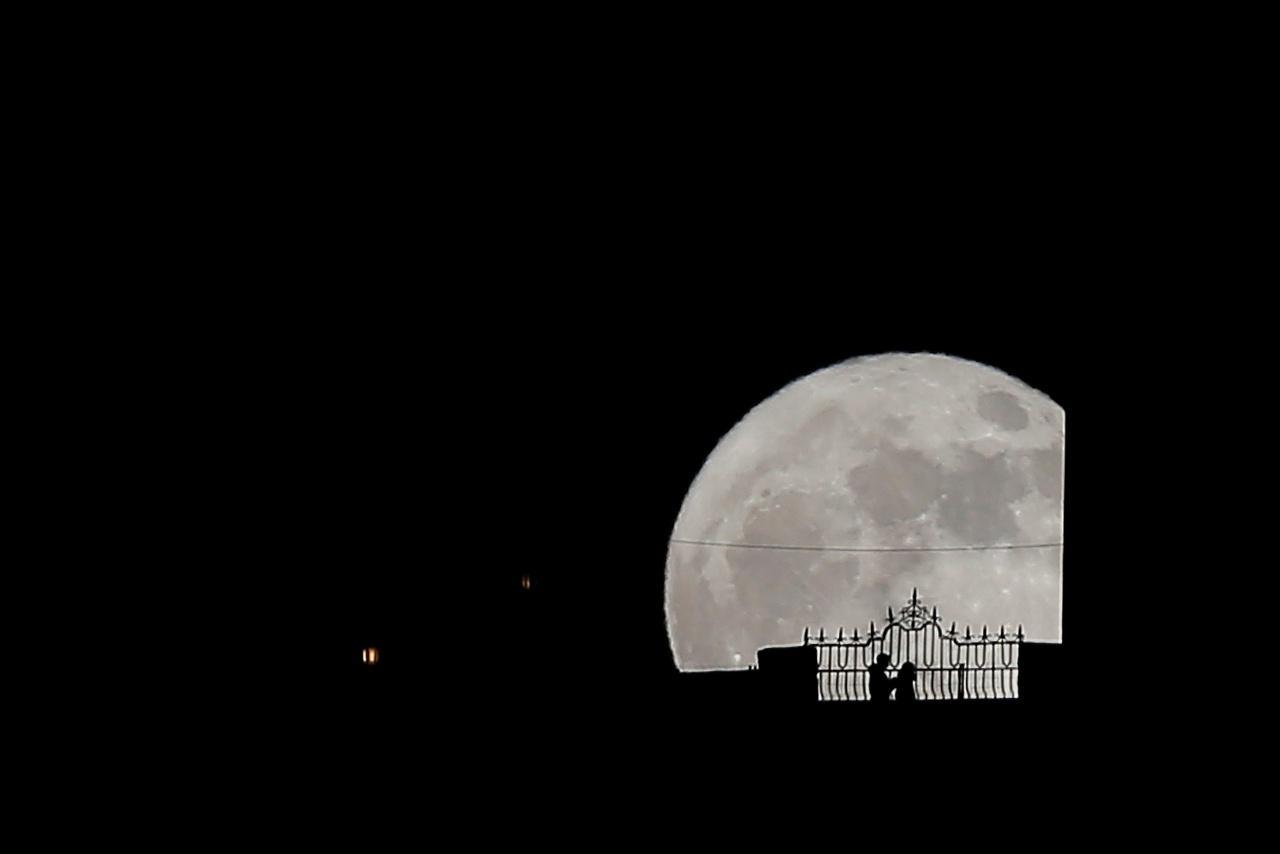 ผู้คนเดินข้ามสะพาน 'ปวนเต นวยโว' ในเมืองรอนดา ของสเปน โดยมีพระจันทร์ดวงใหญ่เป็นฉากหลัง