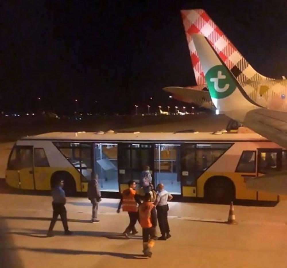 ภาพแสดงให้เห็นเจ้าหน้าที่พยายามนำตัวชายผู้ถูกกล่าวหาว่า กลิ่นตัวเหม็นมาก ขึ้นรถบัสของสนามบิน