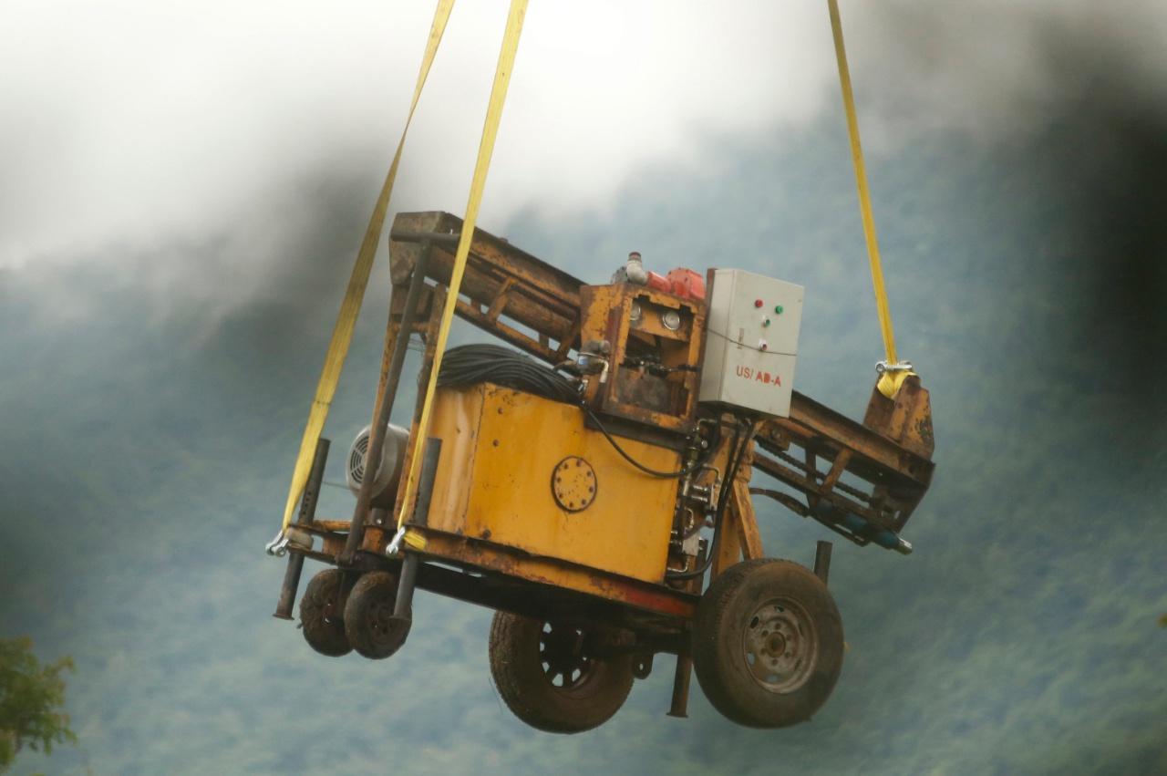 เจ้าหน้าที่ไทยลำเลียงเครื่องขุดเจาะขึ้นไปบนเขาเพื่อหาเส้นทางใหม่เพื่อพาทั้ง 13 ชีวิตออกจากถ้ำ
