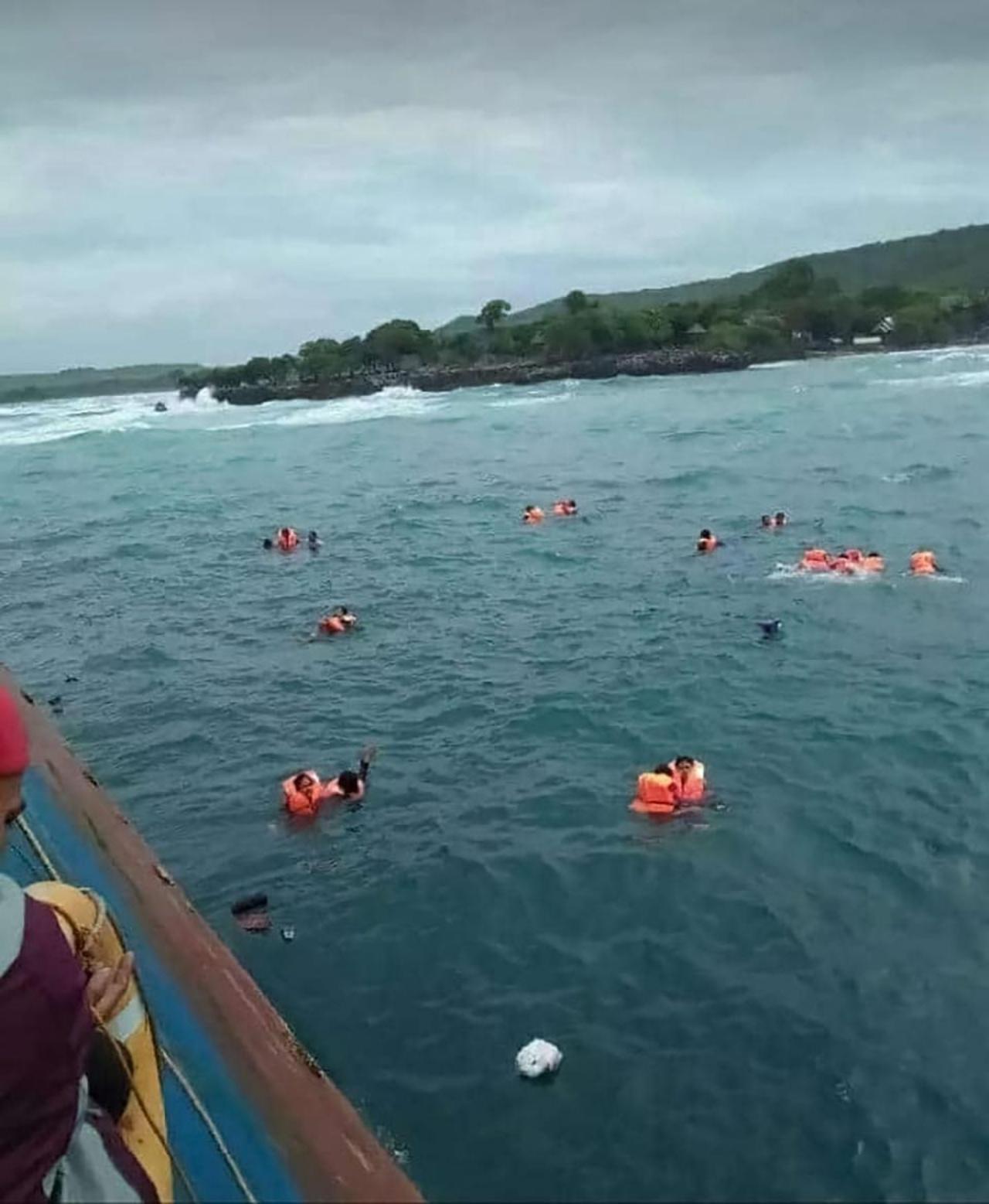 ผู้โดยสารหลายคนใส่เสื้อชูชีพลอยคอรอความช่วยเหลือกลางทะเล