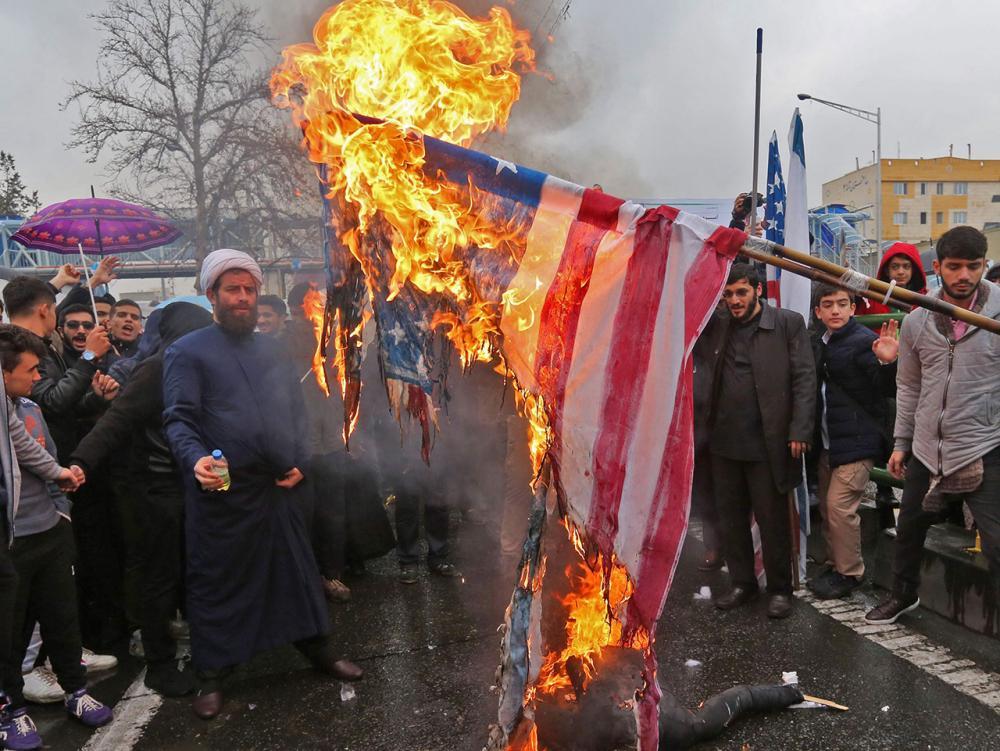 """เกลียดอเมริกา–ฝูงชนชาวอิหร่าน เผาธงชาติสหรัฐฯ และตะโกน """"อเมริกาจงพินาศ"""" ระหว่างการชุมนุมประท้วงในกรุงเตหะราน ในวาระครบรอบ 40 ปี การปฏิวัติอิสลามอิหร่าน เมื่อ 11 ก.พ. (เอเอฟพี)"""
