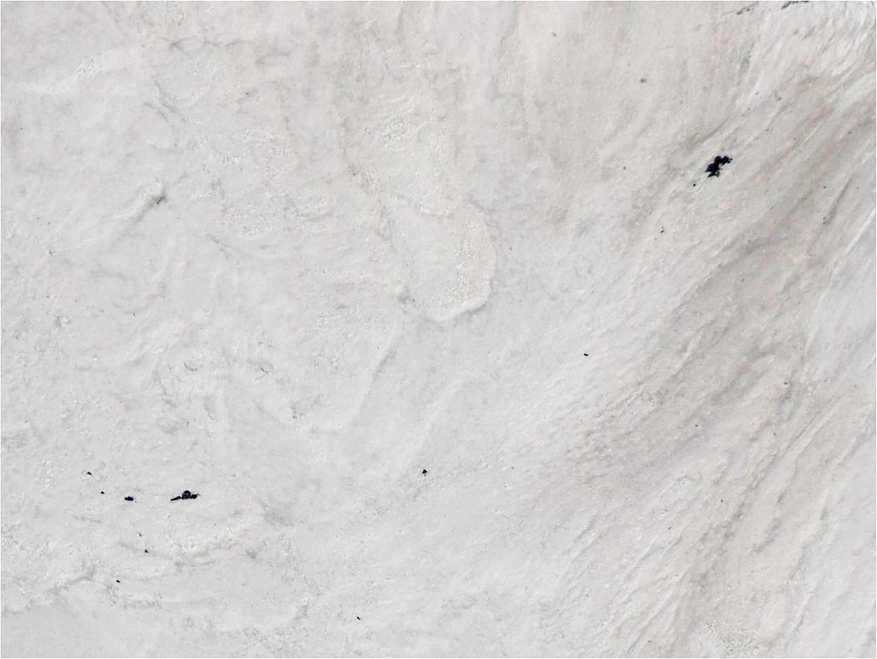 ภาพถ่ายทางอากาศ นักบินอินเดียบนเฮลิคอปเตอร์ บันทึกภาพ แสดงให้เห็นอุปกรณ์ปีนเขาและร่างของนักปีนเขาบางส่วนถูกฝังอยู่ใต้หิมะ