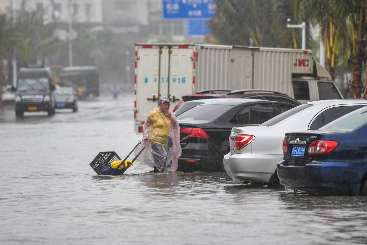 ชาวจีนในมณฑลไห่หนาน หรือไหหลำ เดินลุยน้ำท่วมถนน ขณะเกิดฝนตกหนัก จากอิทธิพลของพายุโซนร้อนวิภา เมื่อ 1 ส.ค.62