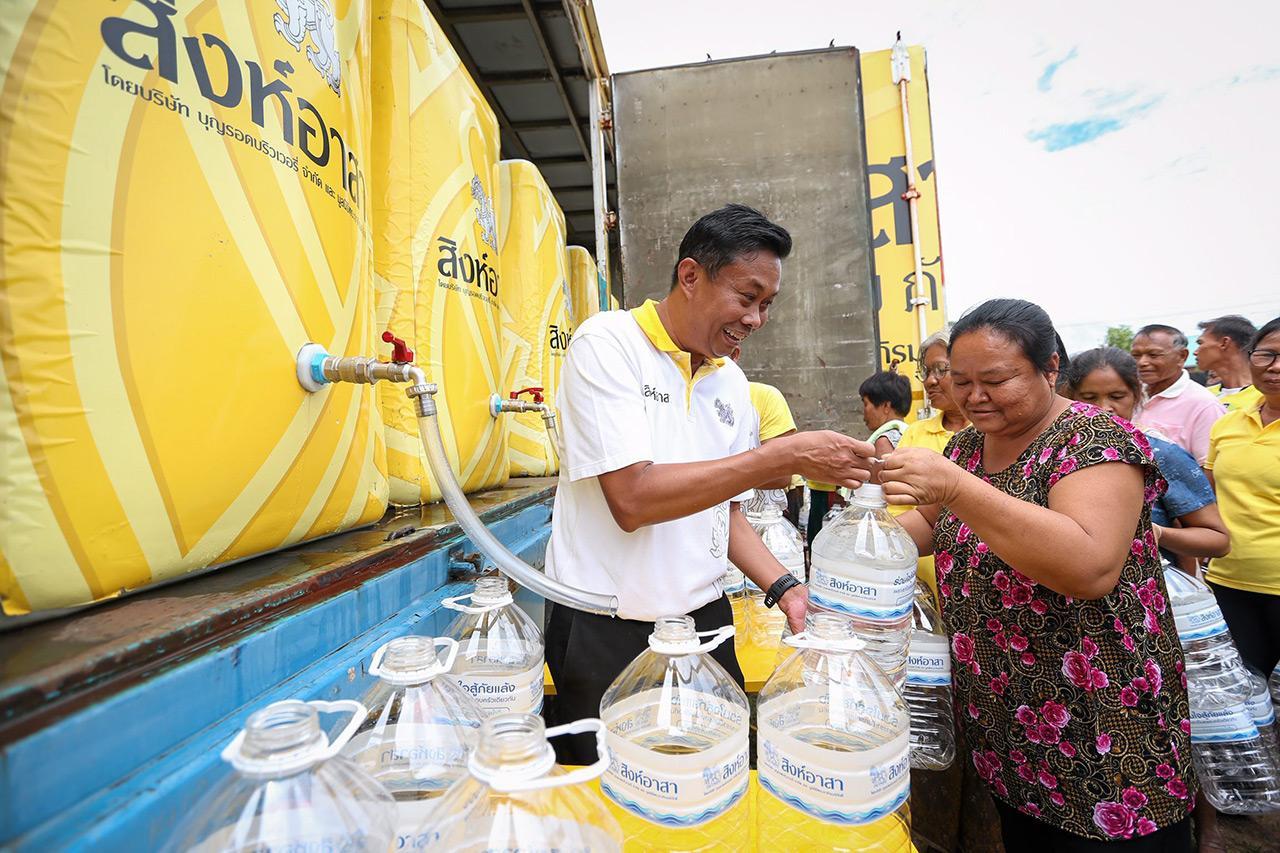 ชาวบ้านหลายคนมองขวดน้ำด้วยความดีใจได้รับน้ำสะอาดบริโภค.