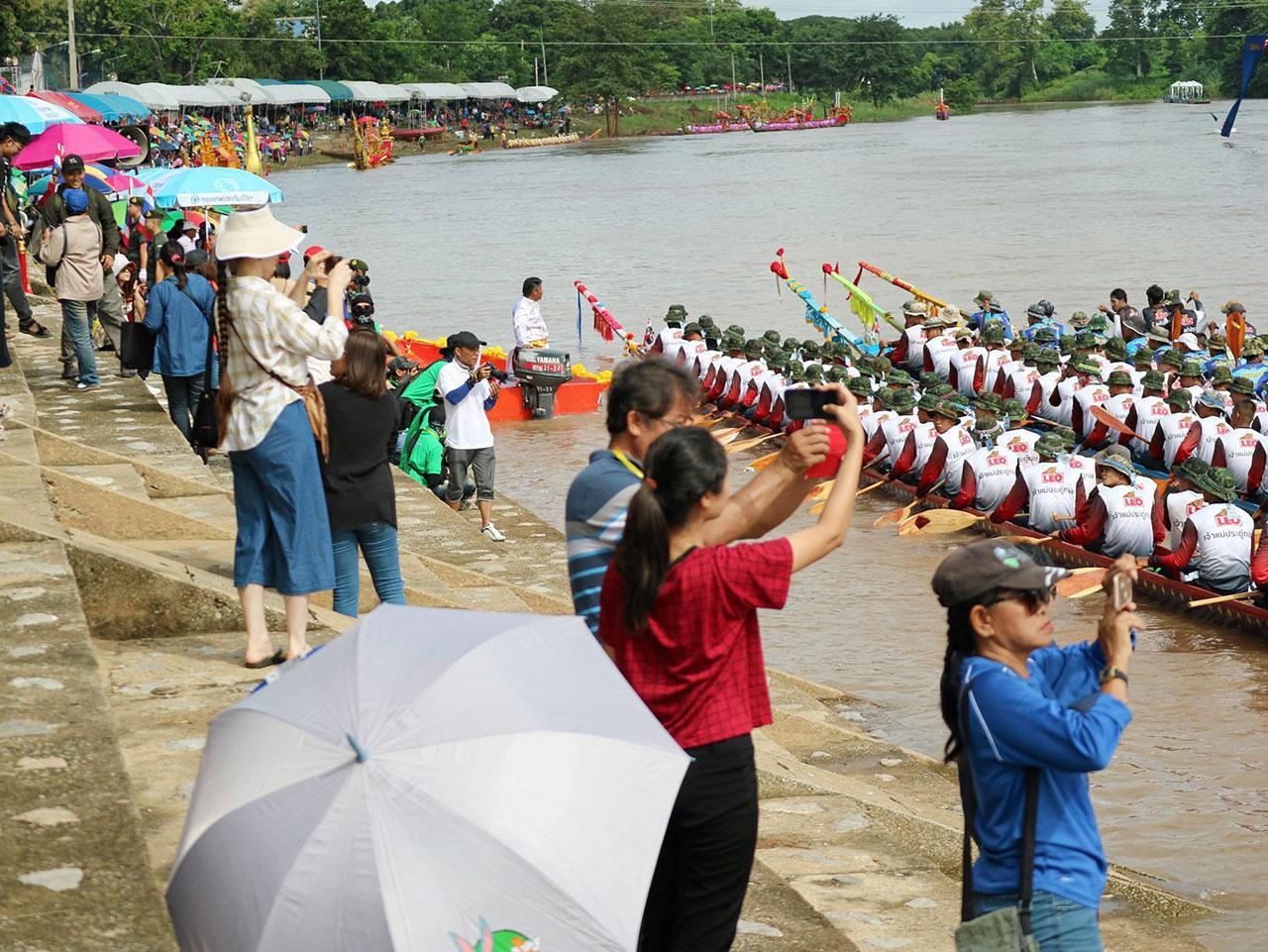 นักท่องเที่ยวพากันถ่ายภาพเรือยาวประเภทต่างๆที่เข้าร่วมการแข่งขัน โดยสองฟากลำน้ำน่านจะคลาคล่ำไปด้วยผู้คนที่เข้าร่วมชมการแข่งขัน.