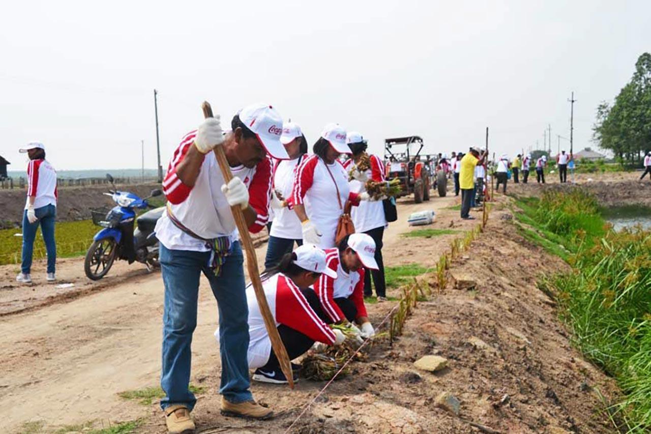 เจ้าหน้าที่และอาสาสมัครช่วยกันขุดดินเตรียมปลูกหญ้าแฝกป้องกันแนวตลิ่งคันคลอง.