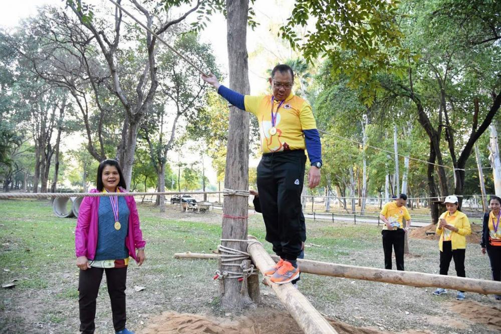 """นายณรงค์ศักดิ์ โอสถธนากร ผวจ.ลำปาง ทดลองเดินไต่ราวไม้ ใน """"สนามเด็กเล่นสร้างปัญญา"""" ภายใน สวนสาธารณะเฉลิมพระเกียรติ (หนองกระทิง) ด้วยความสนใจ."""