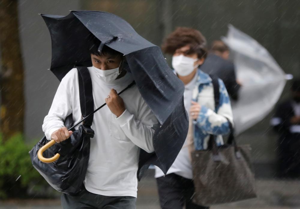 ชาวญี่ปุ่นในกรุงโตเกียวเดินฝ่าฝน จากอิทธิพลของพายุไต้ฝุ่นมินดุลเล