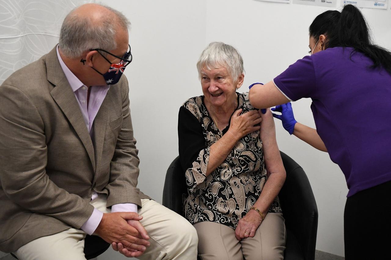 นายกรัฐมนตรี สกอตต์ มอร์ริสัน นั่งอยู่กับคุณยายเจน มาลีเซียค ซึ่งเป็นคนแรกของประเทศที่ได้รับวัคซีนต้านโควิด-19