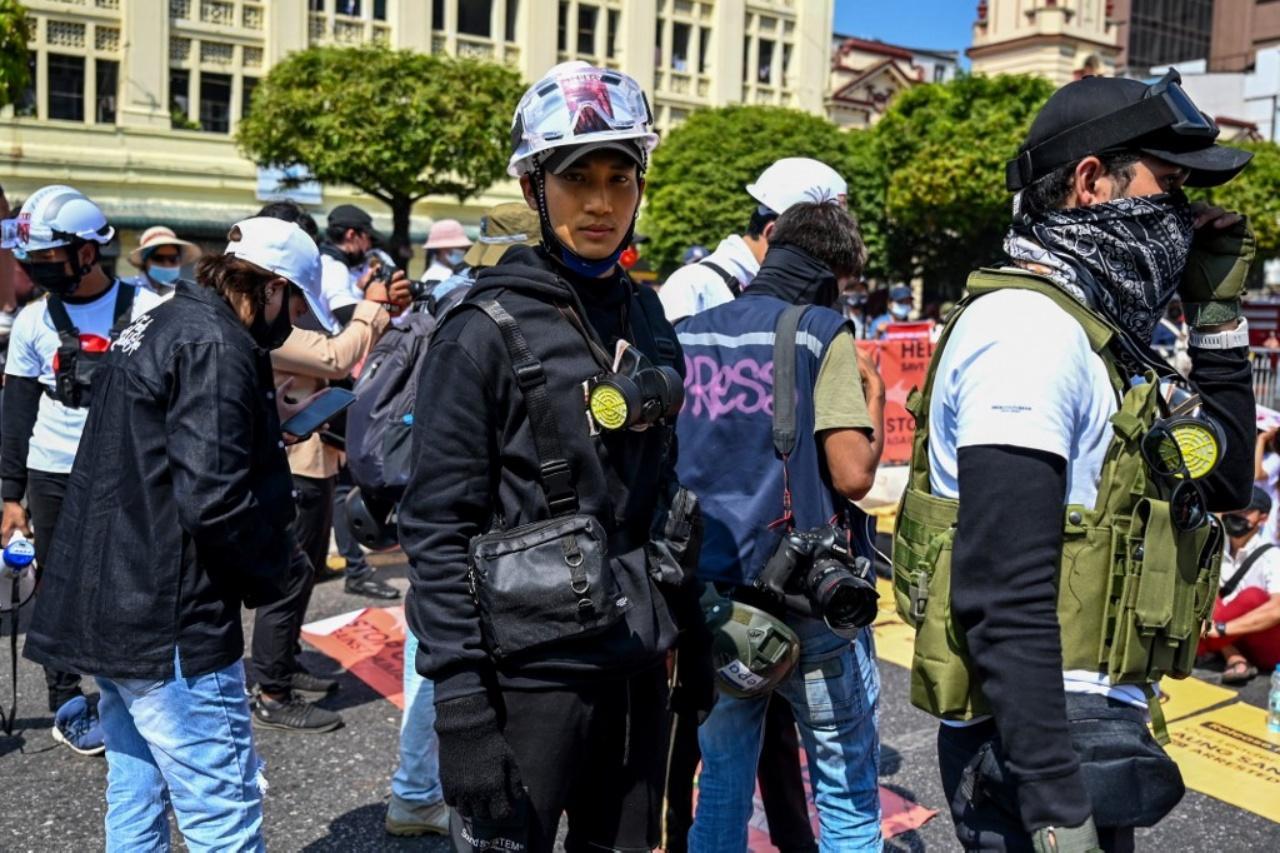 ไป่ ทาคน (คนกลาง) ร่วมชุมนุมต่อต้านรัฐประหาร เมื่อ 17  ก.พ. 64